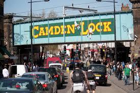 image of busy camden high street capturing famous camden lock overhaead railway bridge.